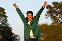 In this April 11, 2021, file photo, Hideki Matsuyama, of Japan, celebrates after putting on the champion's green jacket after winning the Masters golf tournament in Augusta, Ga. (AP Photo/Gregory Bull)