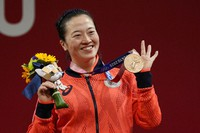 Mikiko Andoh of Japan celebrates on the podium after winning the bronze medal in the women's 59kg weightlifting event, at the Summer Olympics, on July 27, 2021, in Tokyo, Japan. (AP Photo/Luca Bruno)