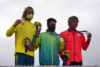 Brazil's Italo Ferreira, center, holds the gold medal, Japan's Kanoa Igarashi, right, silver medal, and Australia's Owen Wright , bronze medal, pose for photographers in the men's surfing competition at the Summer Olympics, on July 27, 2021, at Tsurigasaki beach in Ichinomiya, Japan. (AP Photo/Francisco Seco)