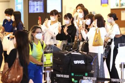 東京オリンピック開幕を前に来日した選手や関係者らに手を振る人たち=羽田空港で2021年7月1日午後4時17分、佐々木順一撮影