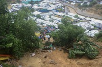 Rohingya refugees and others hold umbrellas as they search for survivors after a landslide triggered by heavy rains in a camp at Ukhiya in Cox's Bazar district, Bangladesh, on July 27, 2021. (AP Photo/ Shafiqur Rahman)