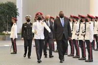 In this photo provided by the Singapore Ministry of Defense, U.S. Defense Secretary Lloyd J. Austin along with Singapore Defense Minister Ng Eng Hen, back, review an honor guard at the Ministry of Defense on July 27, 2021 in Singapore. (Singapore Ministry of Defense via AP)