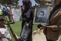 Artists carry portraits of Palestinians who were killed during recent clashes between protesters and the Israeli army in the village, during the opening day of the Beita market, in the West Bank village of Beita, near Nablus, on July 27, 2021. (AP Photo/Nasser Nasser)