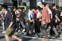 People wearing face masks to protect against the spread of the coronavirus walk on a street in Tokyo on July 27, 2021. (AP Photo/Koji Sasahara)