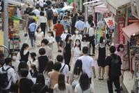 People wearing face masks walk through Takeshita street in Tokyo's Harajuku district, on July 28, 2021. (AP Photo/Koji Sasahara)