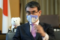 Taro Kono, Japan's minister in charge of vaccinations, wears a mask as he speaks during an interview with The Associated Press at his office in Tokyo on July 28, 2021. (AP Photo/Eugene Hoshiko)