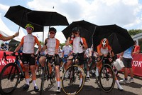 Annemiek van Vleuten, from left, Anna van der Breggen, Demi Vollering and Marianne Vos of the Netherlands protect from the sun with an umbrella before they compete in the women's cycling road race at the 2020 Summer Olympics, on July 25, 2021, in Oyama, Japan. (Michael Steele/Pool Photo via AP)