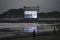 Lifeguards stand on the beach during the surfing competition at the 2020 Summer Olympics, on July 26, 2021, at Tsurigasaki beach in Ichinomiya, Japan. (AP Photo/Francisco Seco)