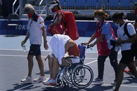 Paula Badosa, of Spain, is helped off the court in a wheelchair after retiring due to illness during the quarterfinals of the tennis competition at the 2020 Summer Olympics, on July 28, 2021, in Tokyo. (AP Photo/Seth Wenig)