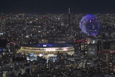 東京五輪の開会式が行われている国立競技場そばの上空を、地球の形を模して編隊飛行するドローン(右上)=東京都渋谷区の渋谷スカイから2021年7月23日午後10時48分、手塚耕一郎撮影