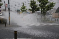A car drives through a flooded street in Fukui on the morning of July 29, 2021. (Mainichi/Sake Toda)