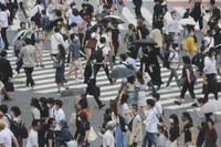 People wearing masks to protect against the spread of the coronavirus cross a street in Tokyo, on July 28, 2021. (AP Photo/Koji Sasahara)