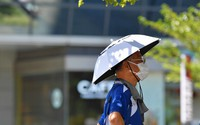 """A Tokyo Olympic volunteer sports an """"umbrella hat"""" as a heat countermeasure in Tokyo's Koto Ward at 10 a.m. on July 25, 2021, as daily temperatures continue to rise above 30 degrees Celsius in the capital. (Mainichi/Yoshiyuki Hirakawa)"""
