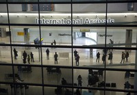 In this file photo dated on Jan. 26, 2021, people in the International Arrivals area at Heathrow Airport in London, during England's coronavirus lockdown.  (AP Photo/Matt Dunham)