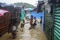 Rohingya refugee children play in flood waters at the Rohingya refugee camp in Kutupalong, Bangladesh, on July 28, 2021. (AP Photo/ Shafiqur Rahman)