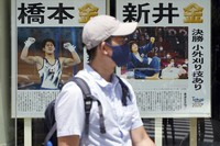 A man wearing a protective mask to help curb the spread of the coronavirus walks past extra papers reporting on Japanese gold medalists at the 2020 Summer Olympics, on July 29, 2021, in Tokyo, Japan. (AP Photo/Eugene Hoshiko)