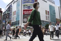 People walk across a crossing near Shimbashi Station in Tokyo on July 29, 2021. (AP Photo/Kantaro Komiya)