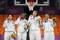 Members of team United States, from left to right, Kelsey Plum, Jacquelyn Young, Stefanie Dolson and Allisha Gray pose with their gold medals during the awards ceremony for women's 3-on-3 basketball at the Summer Olympics, on July 28, 2021, in Tokyo, Japan. (AP Photo/Jeff Roberson)