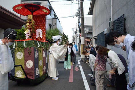 A Shinto priest is seen exorcizing evil spirits for people along the street during a shrine deity parade in Kyoto's Shimogyo Ward on July 19, 2021. (Mainichi/Yoko Minami)
