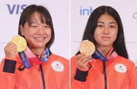 Skateboarders Momiji Nishiya, left, and Funa Nakayama are seen holding their medals the night after winning their events, at a press conference in Tokyo on July 27, 2021. (Pool photo)