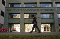 In this Dec. 18, 2020, file photo, a person passes the office of the California Employment Development Department in Sacramento, Calif.  (AP Photo/Rich Pedroncelli)