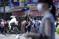 People and police officers wearing face masks to help curb the spread of the coronavirus walk past a busy crossing in Tokyo's Shinjuku district on July 23, 2021, hours before the opening ceremony for the Summer Olympics started. (AP Photo/Kantaro Komiya)