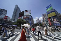 People wearing face masks to help curb the spread of the coronavirus walk across a busy crossing at Shibuya district in Tokyo on July 24, 2021. (AP Photo/Kantaro Komiya)