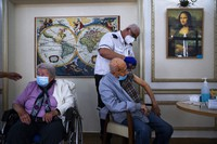 In this Jan. 13, 2021 file photo, a man receives his second Pfizer-BioNTech COVID-19 vaccine from a Magen David Adom national emergency service volunteer, at a private nursing home, in Ramat Gan, Israel. (AP Photo/Oded Balilty)