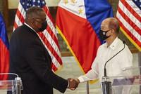 U.S. Defense Secretary Lloyd Austin, left, and Philippine Defense Secretary Delfin Lorenzana shake hands after a bilateral meeting at the Camp Aguinaldo military camp in Quezon City, Metro Manila, Philippines, on July 30, 2021. (Rolex dela Pena/Pool Photo via AP)