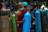 In this July 28, 2021 file photo, a Buddhist monk wearing a face mask holds an oxygen tank for refill outside the Naing oxygen factory at the South Dagon industrial zone in Yangon, Myanmar. (AP Photo)