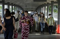 People wearing protective masks pass through a pedestrian bridge on July 30, 2021, in Yokohama. (AP Photo/Kiichiro Sato)