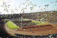 In this Oct. 10, 1964, file photo, balloons fly over Olympians and spectators during the opening ceremony of the 1964 Summer Olympics at the National Stadium in Tokyo. (AP Photo)