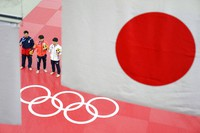 Men's -66kg judo silver medalist Vazha Margvelashvili, of Georgia, from left, gold medalist Hifumi Abe, of Japan, and bronze medalists An Baul, of South Korea, and Daniel Cargnin, of Brazil, obstructed by flag, stand together following the medal ceremony at the Summer Olympics, on July 25, 2021, in Tokyo. (AP Photo/David Goldman)