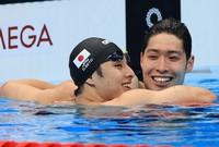 Daiya Seto, left, Kosuke Hagino  of Japan swims in the men's 200-meter individual medley final at the Tokyo Olympics on July 30, 2021. (Mainichi)