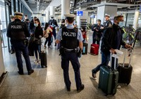 In this March 30, 2021, file photo, German federal police officers check passengers arriving from Palma de Mallorca for a negative Corona test as they arrive at the airport in Frankfurt, Germany. (AP Photo/Michael Probst)