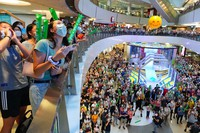 People react as they watch Siobhan Bernadette Haughey of Hong Kong swim in the women's 100-meter freestyle final at the 2020 Summer Olympics, at a shopping mall in Hong Kong, on July 30, 2021. (AP Photo/Vincent Yu)