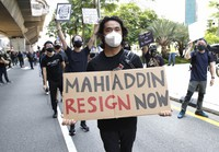 A protester holds placard during a demonstration demanding the prime minister step down near the Independence Square in Kuala Lumpur, on July 31, 2021. (AP Photo/FL Wong)