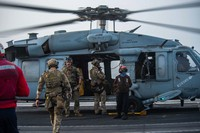 In this photo provided by the U.S. Navy, sailors assigned to an explosive ordnance unit board an MH-60S Seahawk helicopter on the flight deck of aircraft carrier USS Ronald Reagan to head to an oil tanker that was attacked off the coast of Oman in the Arabian Sea on July 30, 2021. (Mass Communication Specialist 2nd Class Quinton A. Lee/U.S. Navy, via AP)