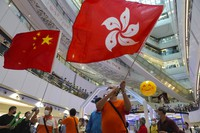 In this July 30, 2021, file photo, people wave a Hong Kong flag and a Chinese national flag as they watch Olympics events at a shopping mall in Hong Kong. (AP Photo/Vincent Yu)