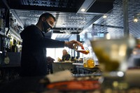 In this April 6, 2021, file photo, bartender Denis Angelov pours drinks at Tin Pan Alley restaurant in Provincetown, Mass. (AP Photo/Steven Senne)