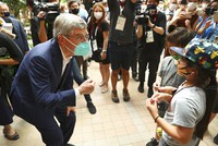 International Olympic Committee (IOC) President Thomas Bach, left, chats with children as he visits the Olympic Agora exhibition in Tokyo on July 30, 2021. (Issei Kato/Pool Photo via AP)