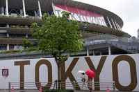 People walk past National Stadium on July 27, 2021, in Tokyo.(AP Photo/Kiichiro Sato)