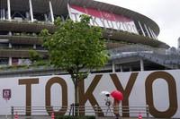 People walk past the National Stadium on July 27, 2021, in Tokyo. (AP Photo/Kiichiro Sato)