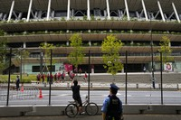 A police officer watches as a man takes pictures of the National Stadium through a fence during the Summer Olympics, on July 29, 2021, in Tokyo. (AP Photo/Jae C. Hong)