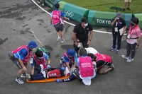 Medics prepare to carry away on a stretcher Connor Fields of the United States after he crashed at the first bend in the men's BMX Racing semifinals at the 2020 Summer Olympics, on July 30, 2021, in Tokyo, Japan. (AP Photo/Ben Curtis)