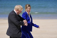 In this file photo dated Saturday, June 12, 2021, British Prime Minister Boris Johnson and his wife Carrie walk on the boardwalk as they prepare to greet guests during the G7 meeting in St. Ives, England. (AP Photo/Kirsty Wigglesworth, FILE)