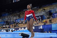 Simone Biles, of the United States, walks after performing on the vault during the artistic gymnastics women's final at the 2020 Summer Olympics, Tuesday, July 27, 2021, in Tokyo. (AP Photo/Ashley Landis)