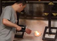 A craftsman places a blowpipe in a furnace and spools molten glass onto its end at Shinohara Furin Honpo in Tokyo's Edogawa Ward on July 8, 2021. (Mainichi/Akinori Miyamoto)