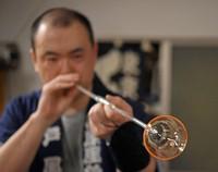 Craftsman Yoshihiro Hamada is seen blowing into a pipe to inflate glass into the shape of a bell at Shinohara Furin Honpo in Tokyo's Edogawa Ward on July 8, 2021. (Mainichi/Akinori Miyamoto)