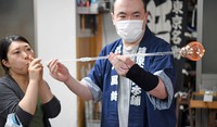 A customer, left, is seen taking part in a glassblowing workshop session at Shinohara Furin Honpo in Tokyo's Edogawa Ward on July 8, 2021. (Mainichi/Akinori Miyamoto)